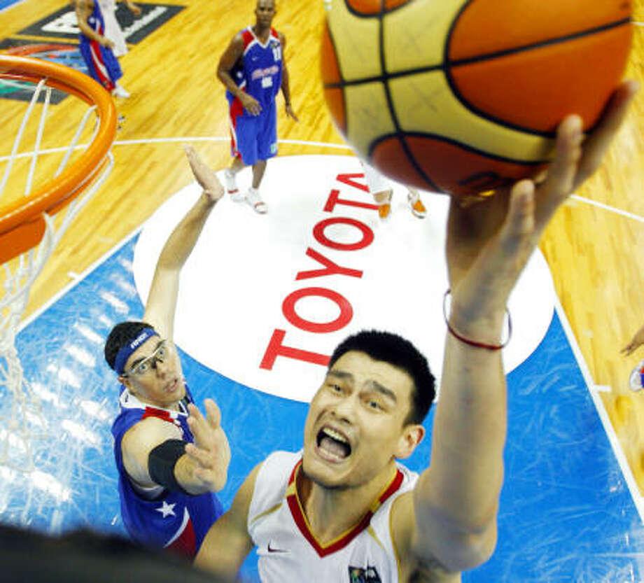 China's Yao Ming puts up a shot as Puerto Rico's Daniel Santiago guards. Photo: MARK J. TERRILL, AP