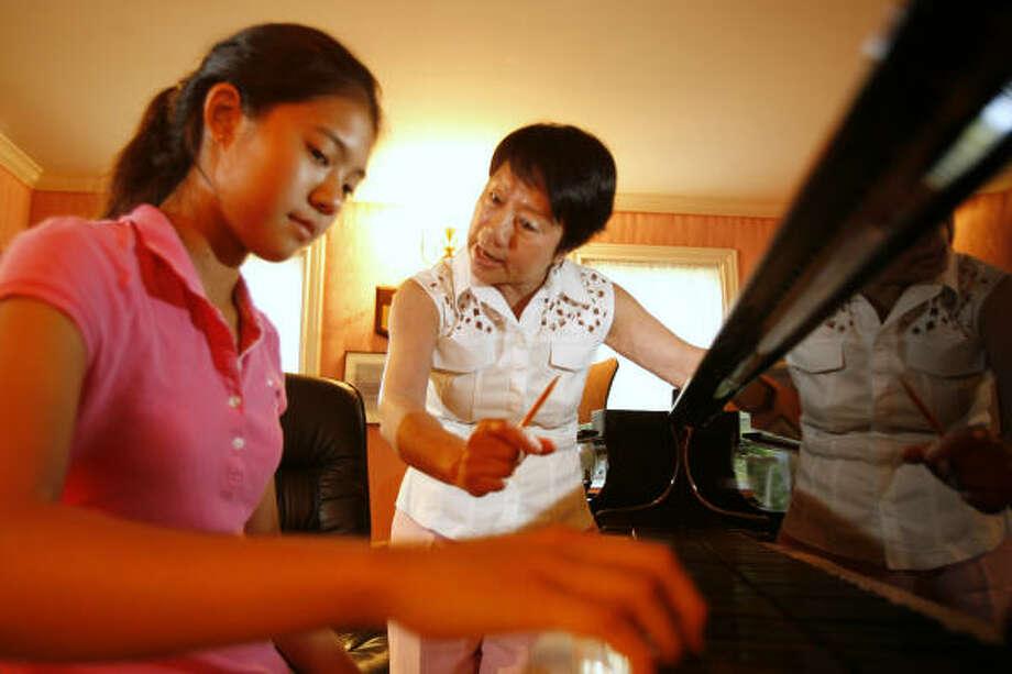 Shu-Hao Pao, right, works with top pupil Mia Nishikawa, 14. Photo: Kevin Fujii, Chronicle