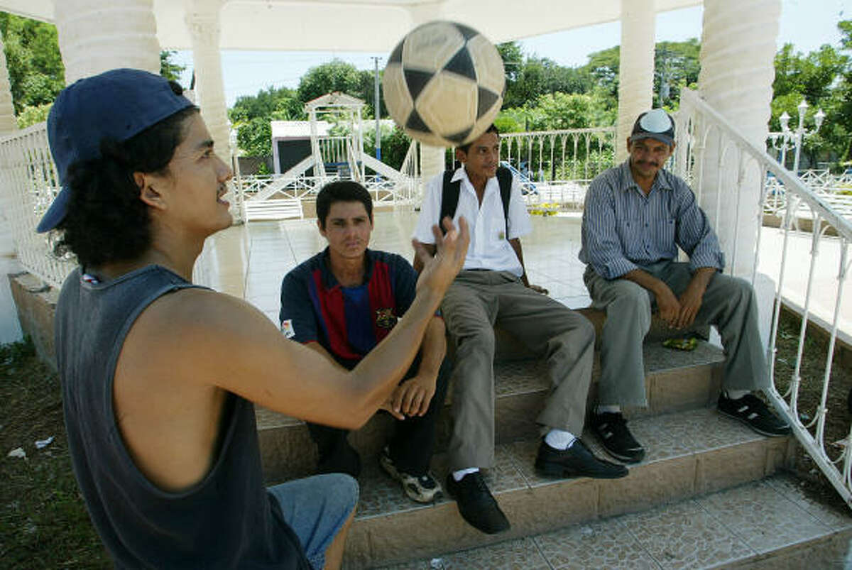 Carlos Avila, 26, chats with friends in El Carmen, El Salvador. Avila receives remittances from family members living in Virginia and Houston. Remittances from abroad made up more than 16 percent of the country's gross domestic product in 2005.