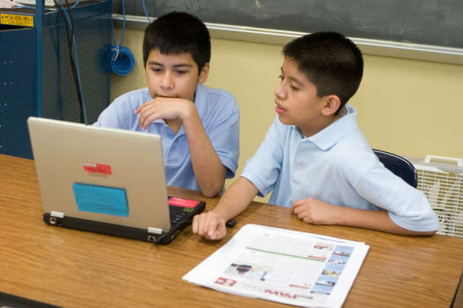 Eighth-graders Hugo Castillo, left, and René Gamboa, both 13, work on the layout for the next issue of Marshall Middle School's award-winning newspaper, Paw Print. Photo: R. Clayton McKee, For The Chronicle