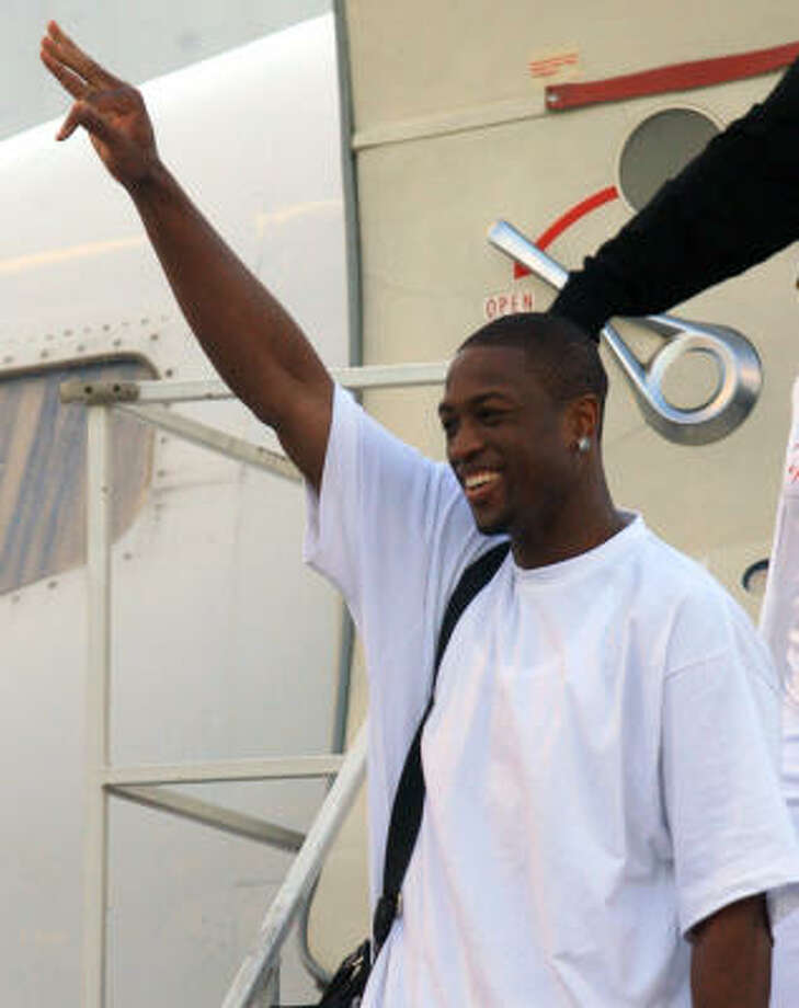 Heat 's Dwyane Wade waves to fans after arriving at Miami International Airport Wednesday. Photo: LUIS M. ALVAREZ, ASSOCIATED PRESS