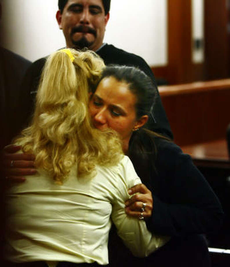 Sharon Tuck, left, mother of defendant David Tuck, and the victim's mother embrace after David Tuck was sentenced to life in prison. The victim's father is in the background. Photo: Steve Ueckert, Chronicle