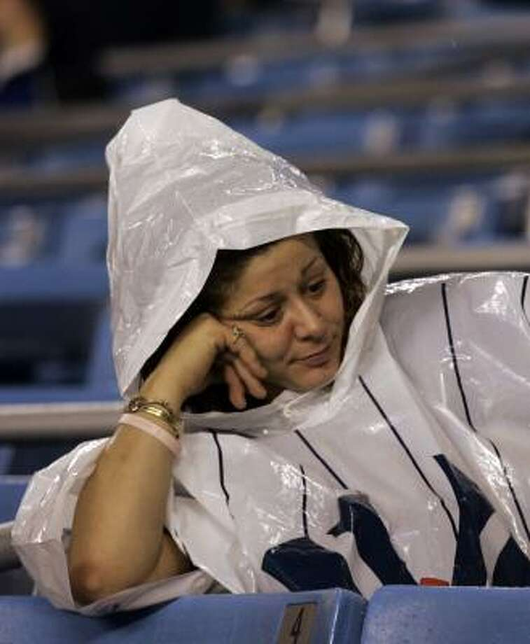 Yankees fan Mary Willis tries to wait out the storm. Photo: KATHY WILLENS, AP