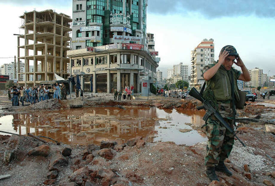A Lebanese soldier stands next to a crater following Israeli airstrikes at the main Mar Mikhail crossroads in southern Beirut, Lebanon, today. Photo: PIERRE BOU KARAM, AP