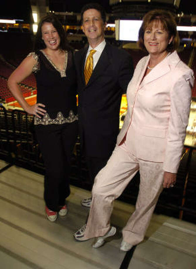 Barry Mandel, president and CEO of the Houston Downtown Alliance, is flanked by Heart of the City Gala chairs Ashley Nichols, left, and Georgianna Nichols. All three were in tennis shoes, required footwear for shooting hoops and dancing on the floor of the Toyota Center, where the dinner was held. Photo: Dave Rossman, For The Chronicle