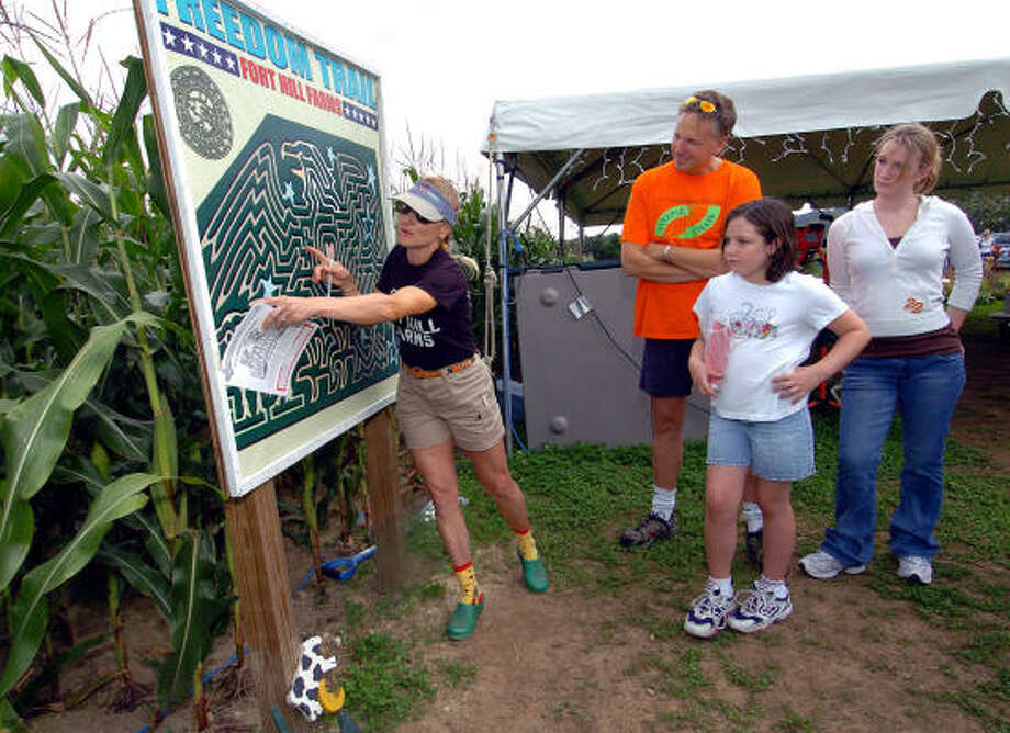 Kristin Orr, left, explains how to navigate the corn maze at her Fort Hill Farms in Thompson, Conn., to customers Walter Milestone, Victoria Trudeau-Mungham and Marissa Mungham. Photo: JESSICA HILL, AP