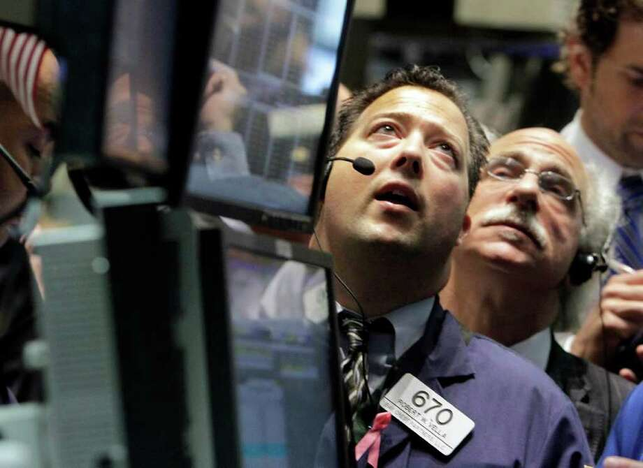 Traders Robert Vella, left, and Peter Tuchman work on the floor of the New York Stock Exchange Thursday, Aug. 11, 2011. (AP Photo/Richard Drew) Photo: Richard Drew