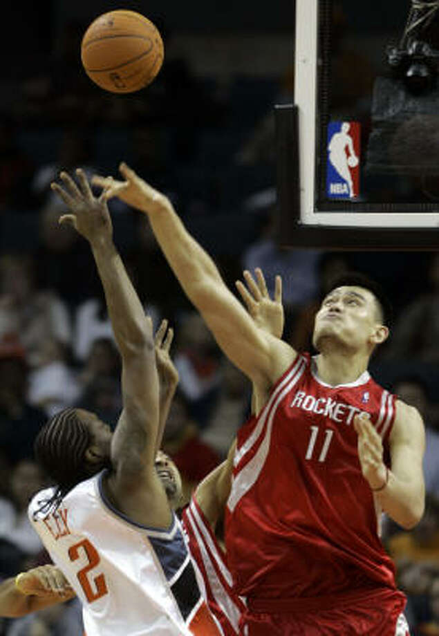 Yao Ming swats away Melvin Ely's shot during Friday's game. Photo: CHUCK BURTON, AP
