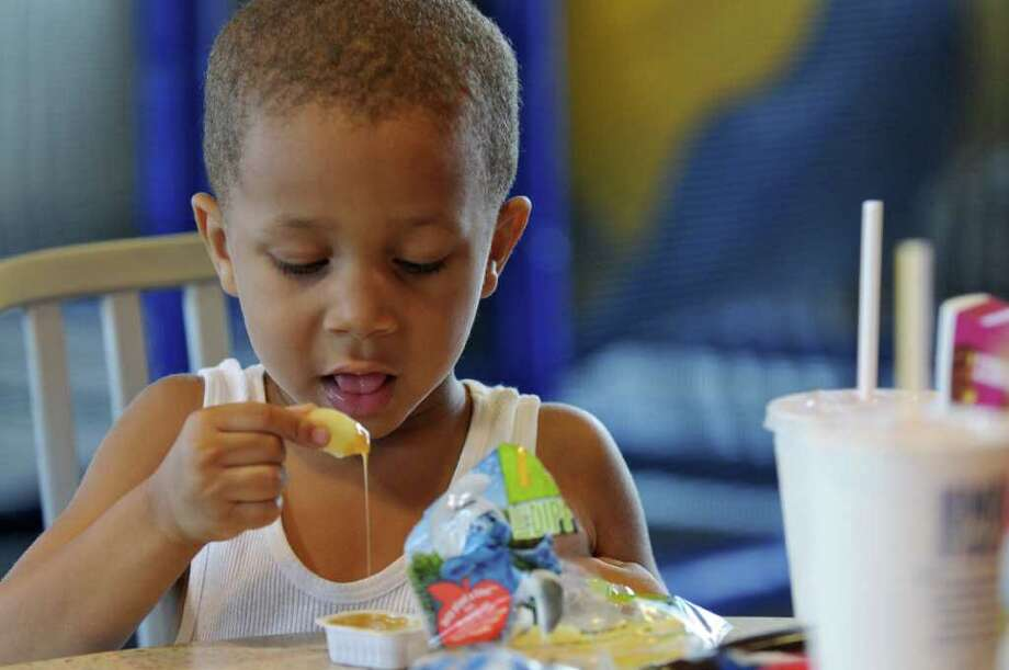Keith Cordell, 4, eats an Apple Dipper while dipping it into caramel sauce during lunch at the McDonald's on Thursday Aug. 11, 2011 in Watervliet, NY.  (Philip Kamrass / Times Union) Photo: Philip Kamrass / 00014230A