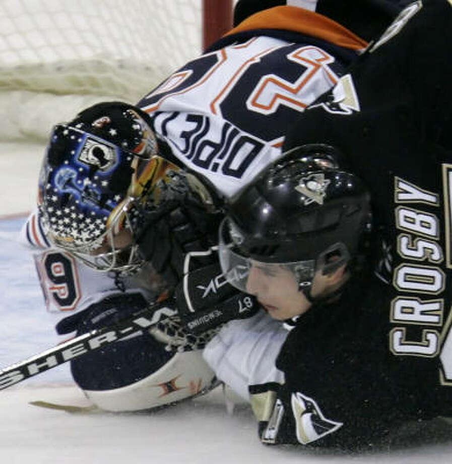Pittsburgh's Sidney Crosby and the New York Islanders' Rick DiPietro hit the ice. The host Penguins won 3-2. Photo: GENE J. PUSKAR, AP