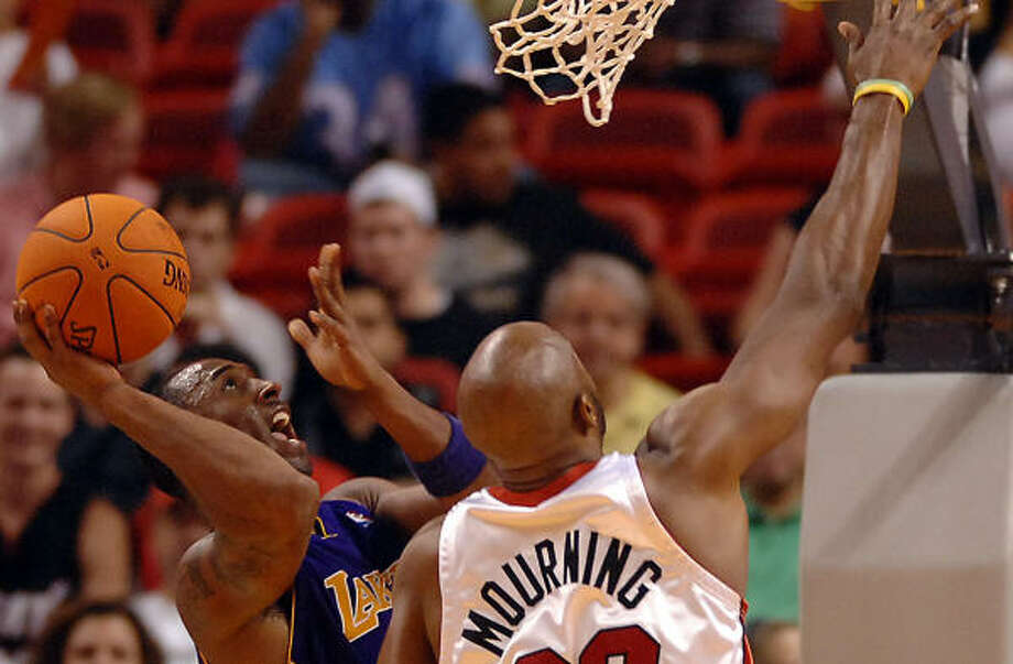 Kobe Bryant (24) tries to shoot past Alonzo Mourning during the third quarter. Bryant scored just 16 points against the Heat, one over his season-low. Photo: Steve Mitchell, AP