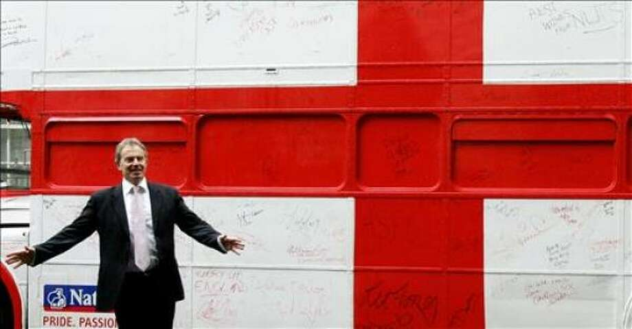 British Prime Minister Tony Blair looks at the side of a double decker bus, decorated with the St. George's flag of England design and autographed by celebrities at 10 Downing Street in London, 24 May 2006. The bus has been prepared especially for a charity soccer event entitled 'Soccer Aid' which will be held in Manchester 27 May, and from which all financial proceeds will be donated to the children's charity UNICEF. AFP PHOTO/CARL DE SOUZA Photo: CARL DE SOUZA, AFP