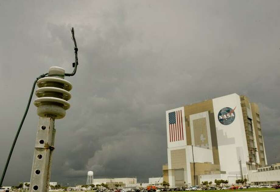 A cable made to absorb a lightning strike stands near electrical boxes close by NASA's Vehicle Assembly Building today as thunderclouds are seen in the distance at the Kennedy Space Center in Cape Canaveral, Fla. Photo: Mark Wilson, Getty Images