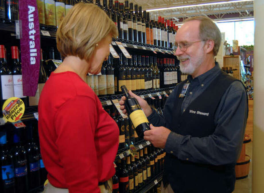 Woodlands resident D'Ann Salatka gets help selecting a wine during a recent trip to the store from Market Street H-E-B wine steward Steve Osburn. Photo: David Hopper, For The Chronicle