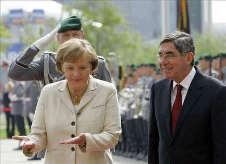 German Chancellor Angela Merkel (L) and Costa Rican President Oscar Arias Sanchez (R) inspect an honor guard 09 June 2006 at the Chancellery in Berlin. They met for bilateral talks. In the evening, the national football teams of the two countries will open the FIFA Football World Cup 2006.    AFP PHOTO    DDP/JOHANNES EISELE     GERMANY OUT Photo: JOHANNES EISELE, AFP