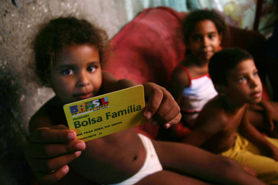 Children of Ana Paula dos Santos show their Bolsa Familia card. The program encourages the poor to keep children in school. Photo: Marcelo Salinas, For The Chronicle