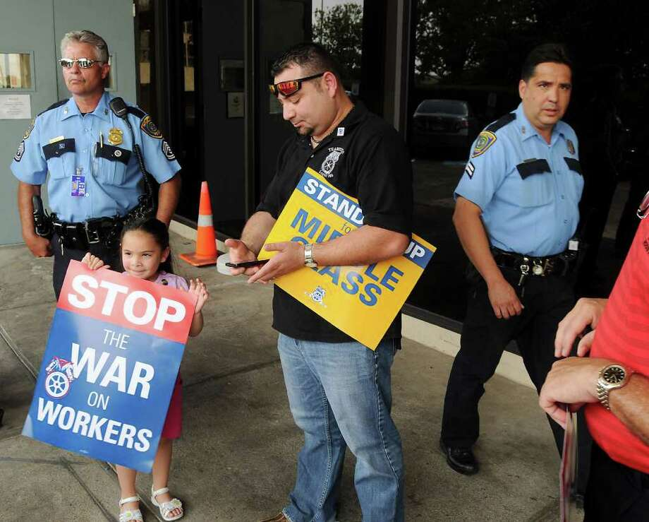 Local Teamster member Jorge Lizama and his daughter Hailey,8, are asked to leave the property after protesting US Congressman John Mica, 7th District of Florida Chairman of the House Transportation & Infrastructure Committee, while he was attending  an I-69 meeting at the IAH Mariott Hotel Thursday Aug. 11,2011.(Dave Rossman/For the Chronicle) Photo: Dave Rossman, Freelance / © 2011 Dave Rossman