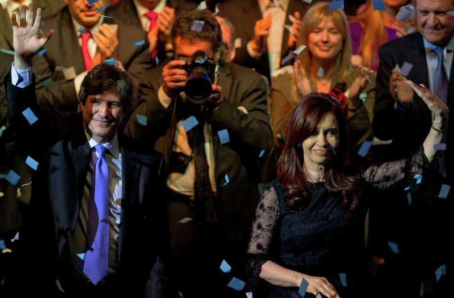 Argentina's President and candidate for re-election Cristina Fernandez, right, and her Economy Minister and vice-presidential candidate Amado Boudou wave to the crowd during an election rally in Buenos Aires, Argentina, Wednesday Aug. 10, 2011. Argentines will hold primary elections for the first time on Aug. 14 ahead of the presidential election which is scheduled for Oct. 23. (AP Photo/Victor R. Caivano) Photo: Victor R. Caivano, STF / AP2011