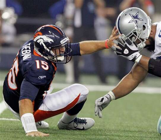 Denver Broncos quarterback Tim Tebow, left, helps Dallas Cowboys defensive end Jason Hatcher put his helmet back on during the second quarter of a preseason NFL football game on Thursday, Aug. 11, 2011, in Arlington, Texas. (AP Photo/LM Otero) Photo: LM Otero, Associated Press / AP