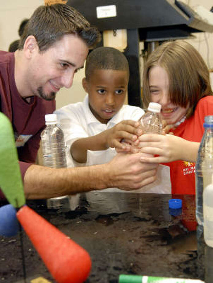 San Jacinto College chemistry student Richard Wilder assists Jamiel Roberson, center, and Melissa Snitoff, both fourth-graders from Mark Twain Elementary School in Houston, during the college's observance of National Chemistry Week. The pupils find that squeezing a bottle of water with an upside-down, half-full test tube inside causes the test tube to sink. Releasing the squeeze makes the tube float. Photo: Kim Christensen, For The Chronicle