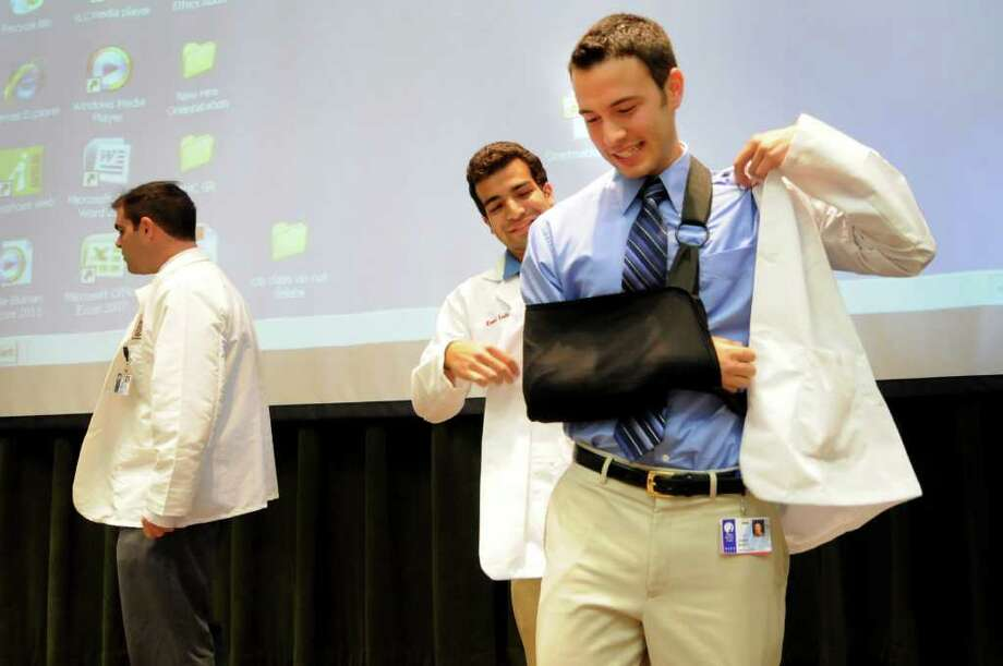 First-year medical student John Shultz of Altamont, right, gets initiated into the medical community as he puts on a white coat, with help from a second-year student, during the White Coat Ceremony on Thursday, Aug. 11, 2011, at Albany Medical College in Albany, N.Y. (Cindy Schultz / Times Union) Photo: Cindy Schultz