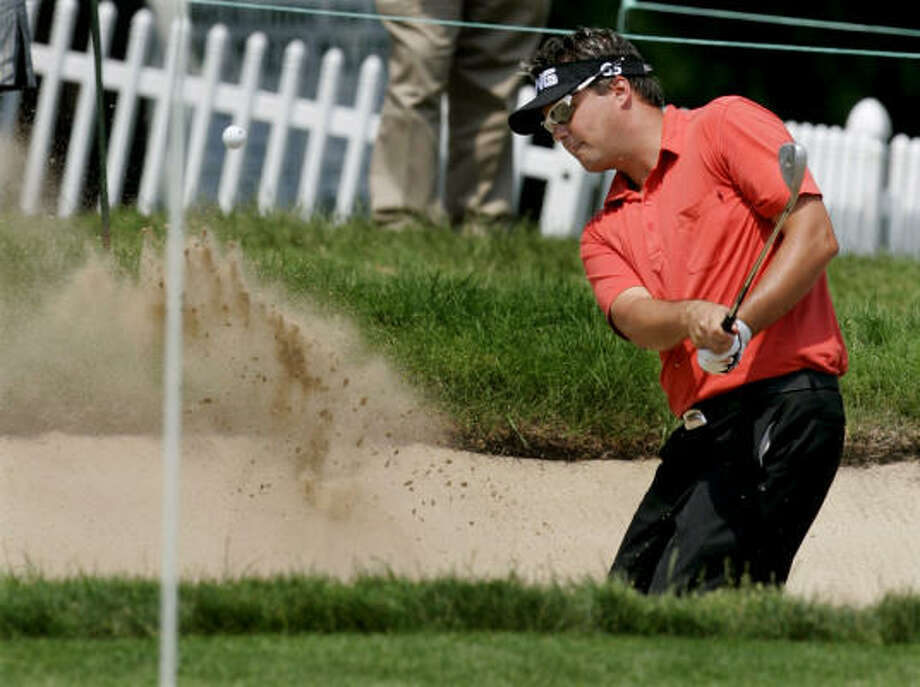 Leader Daniel Chopra sinks a shot for birdie out of a bunker on the 18th hole during the second round of the Western Open on Friday. Photo: JEFF ROBERSON, ASSOCIATED PRESS
