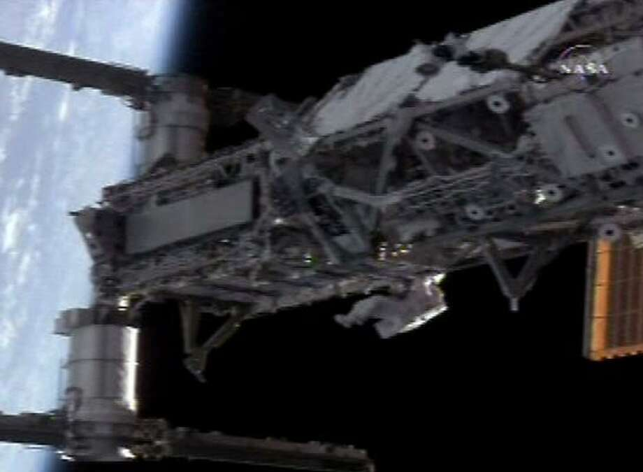 Spacewalker Heidemarie Stefanyshyn-Piper (bottom) installs power and data cables to make the P3/P4 truss operational during the extravehicular excursion from the International Space Station in this view from NASA TV. Photo: NASA TV, REUTERS