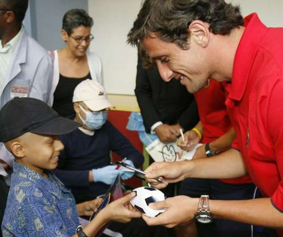 FC Barcelona player Juliano Belletti signs an autograph on Monday for patient Mohamed Alamoudi at Children's Hospital at University of Texas M. D. Anderson Cancer Center. Photo: Steve Campbell, Houston Chronicle