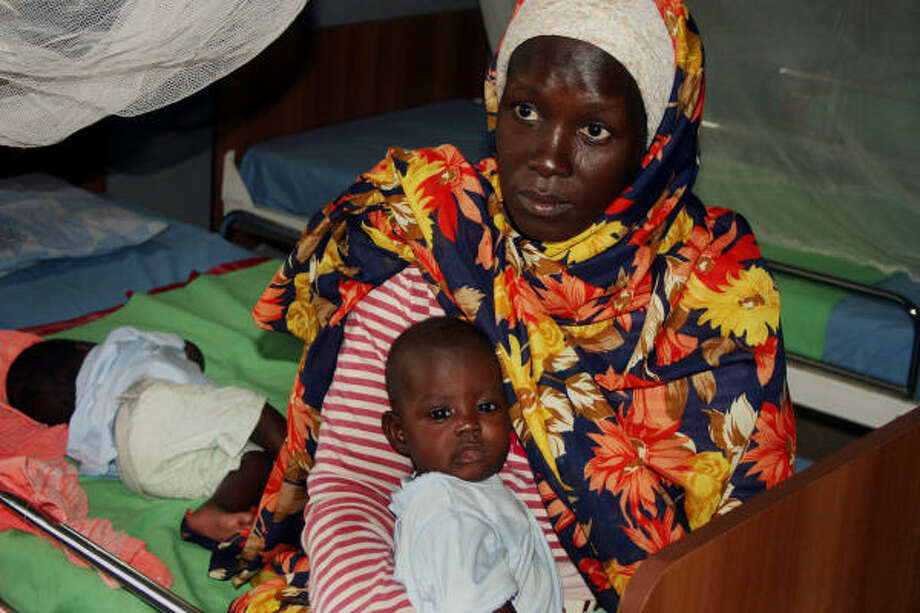 Myriam Ibrahim, 28, holds 4-month-old Fayrous as sibling Fardous sleeps at a clinic in North Darfur. Fawzia, the third triplet, died a month ago from malnutrition. The U.N. Children's Fund estimates about 80 children under 5 die each day in Darfur. Photo: ALFRED DE MONTESQUIOU, AP