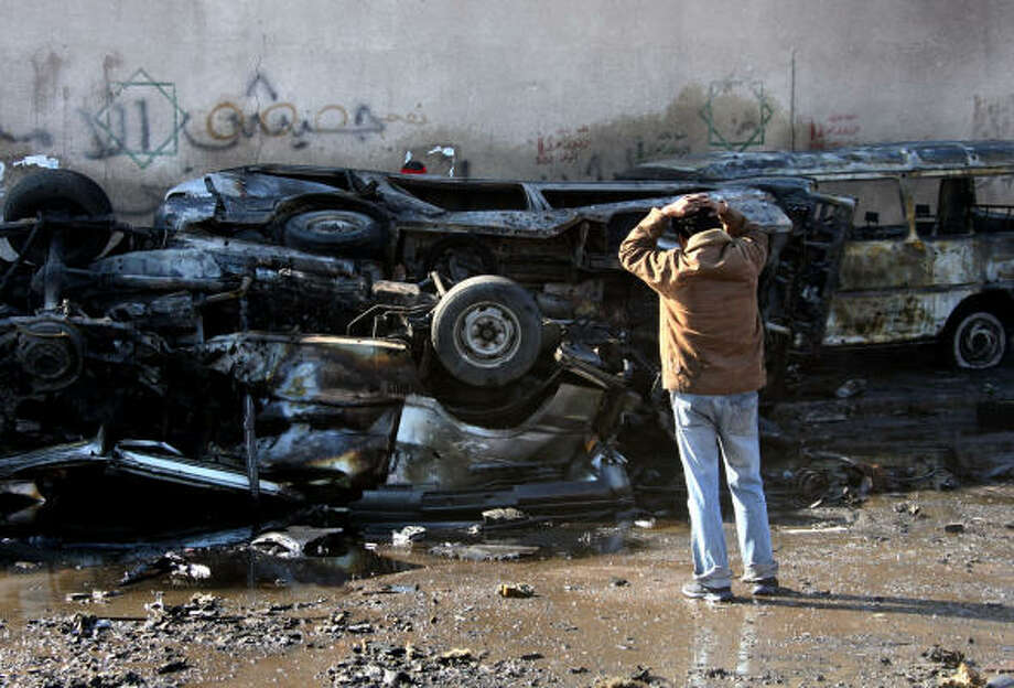 An Iraqi looks at destroyed cars at the scene of an attack Tuesday in a mostly Shiite neighborhood in Baghdad. Three parked cars exploded one after another, killing at least 25. Photo: KHALID MOHAMMED, AP