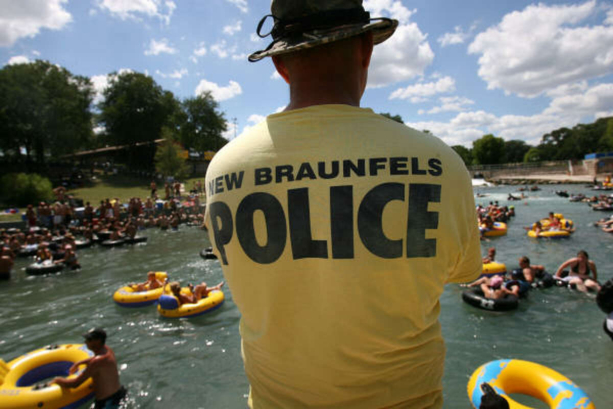 An officer keeps an eye on Comal River tubers. Some nearby homeowners are complaining about lewd behavior, alcohol and loud music in the once-family-friendly tourist spot. A former senator called parts of the area