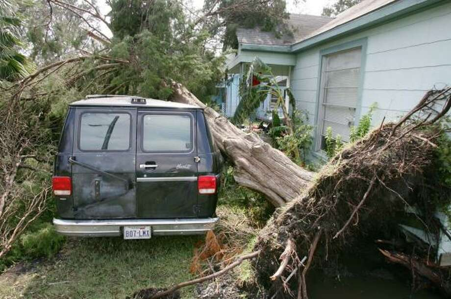 An uprooted tree lies in front of a Port Arthur home after Hurricane Rita in September 2005. Major insurance companies are trimming coverage along the Texas Gulf Coast. Photo: RODGER MALLISON, KRT