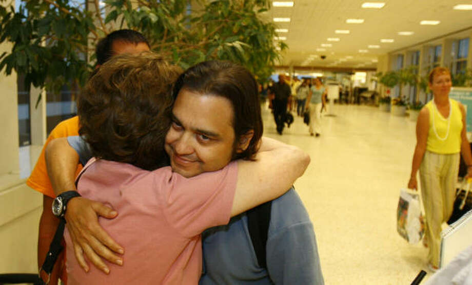 Kevin Lozada of The Woodlands gets a hug from his mom, Gloria Lozada, after his flight became an ordeal. Photo: Nick De La Torre, CHRONICLE