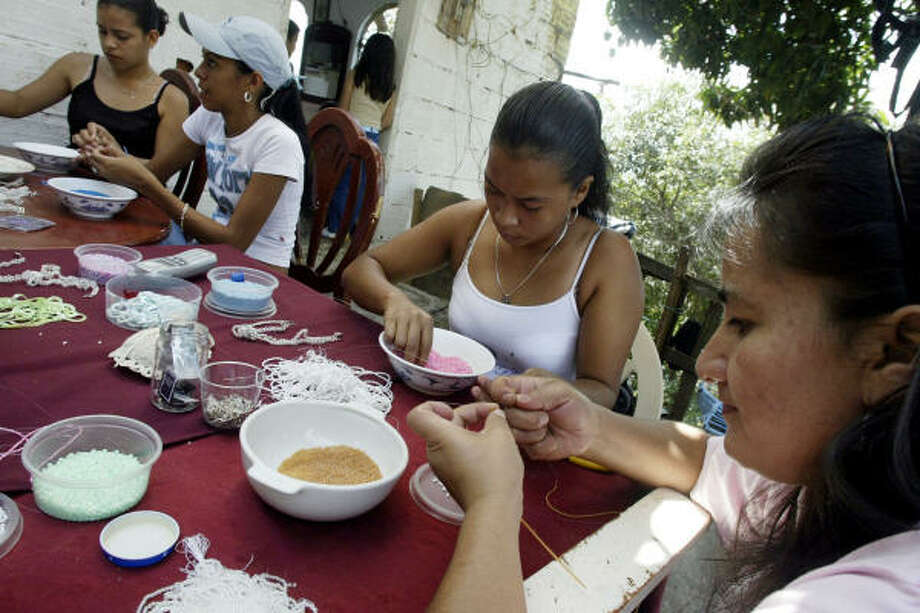 Women string beads in Los Chorros neighborhood of Cali, Colombia, to form lingerie straps for an Ohio company called Strappity-do-da. Photo: INALDO PEREZ, AP