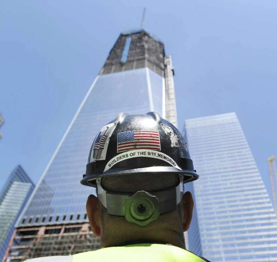 Chris Powers of KC Fabrications, Inc., of Gardiner, N.Y., the company constructing the memorials at the Freedom Tower, looks skyward toward the tower in New York City, Thursday, Aug. 11, 2011, that is under construction a month before the 10th anniversary of 9/11.  Bob Lucky/Hearst Newpapers Photo: Bob Luckey, Staff Photographer / Greenwich Time