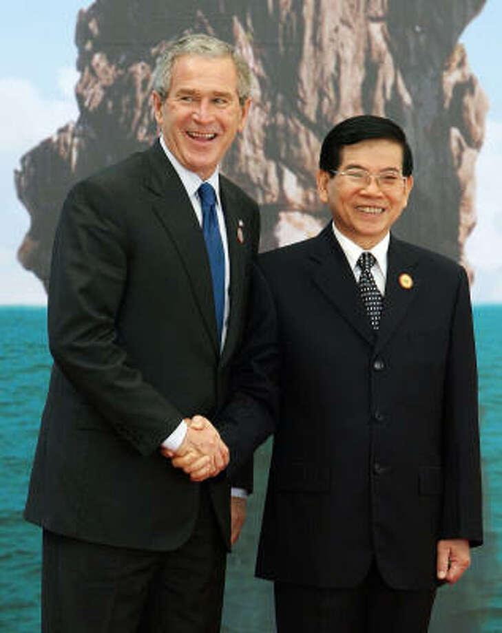 President Bush greets his Vietnamese counterpart, Nguyen Minh Triet, before Saturday's Asia Pacific Economic Cooperation summit in Hanoi, Vietnam. Photo: TOSHIFUMI KITAMURA, AP
