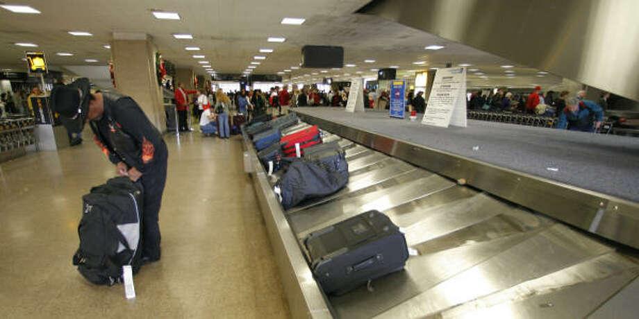Heriberto Cirlos III picks up his luggage Wednesday at George Bush Intercontinental Airport. Photo: Steve Campbell, Chronicle