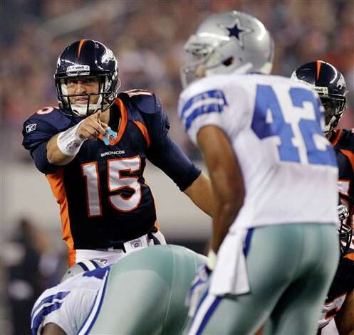 Denver Broncos quarterback Tim Tebow makes a call as Dallas Cowboys safety Barry Church looks down the line during the second quarter of a preseason NFL football game Thursday, Aug. 11, 2011, in Arlington, Texas. (AP Photo/Tony Gutierrez) Photo: Tony Gutierrez, Associated Press / AP