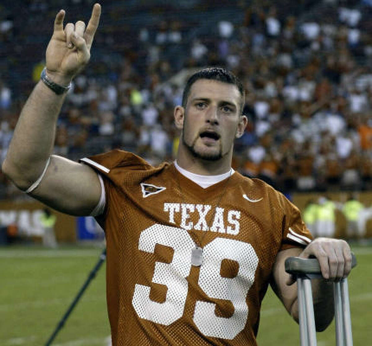 Texas defensive end Brian Robison had to use crutches, but was on the field with the Longhorns after the game.