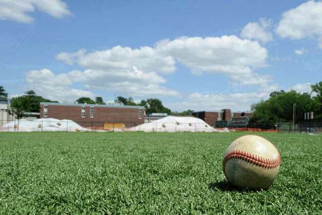 School officials announced that all Greenwich High School playing fields would be closed in July after testing discovered PCB toxins that exceed regulatory standards near the fields. District officials began testing soil samples after workers on the school's new auditorium project discovered contaminated soil earlier in July. Pictured is the artificial turf field to the west of the school Wednesday, July 27, 2011, with the excavation site in the background. Photo: File Photo / Greenwich Time File Photo