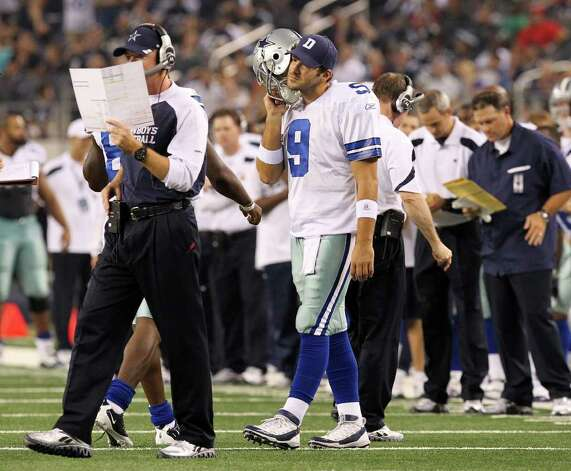 Dallas Cowboys' Tony Romo (09) keeps a close ear to his helmet's communication device as head coach Jason Garrett calls in the two-point conversion play against the Denver Broncos in the fourth quarter of their pre-season football game at Cowboys Stadium in Arlington, Texas on Thursday, August 11, 2011.  Cowboys defeated the Broncos 24-23. Kin Man Hui/kmhui@express-news.net Photo: KIN MAN HUI, -- / San Antonio Express-News