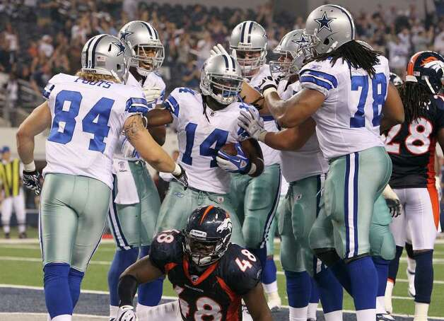 Dallas Cowboys' Dwayne Harris (14) gets congratulated by teammates after making a catch for a touchdown as Denver Broncos' Braxton Kelley (48) lays on the ground late in the fourth quarter of their pre-season football game at Cowboys Stadium in Arlington, Texas on Thursday, August 11, 2011.  Cowboys defeated the Broncos 24-23. Kin Man Hui/kmhui@express-news.net Photo: KIN MAN HUI, -- / San Antonio Express-News