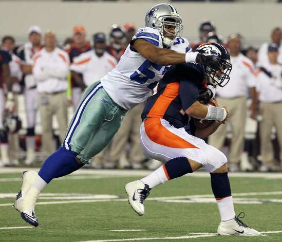 Dallas Cowboys' Victor Butler (57) sacks Denver Broncos quarterback Tim Tebow (right) in the first half of their pre-season football game at Cowboys Stadium in Arlington, Texas on Thursday, August 11, 2011.  Kin Man Hui/kmhui@express-news.net Photo: KIN MAN HUI, -- / San Antonio Express-News