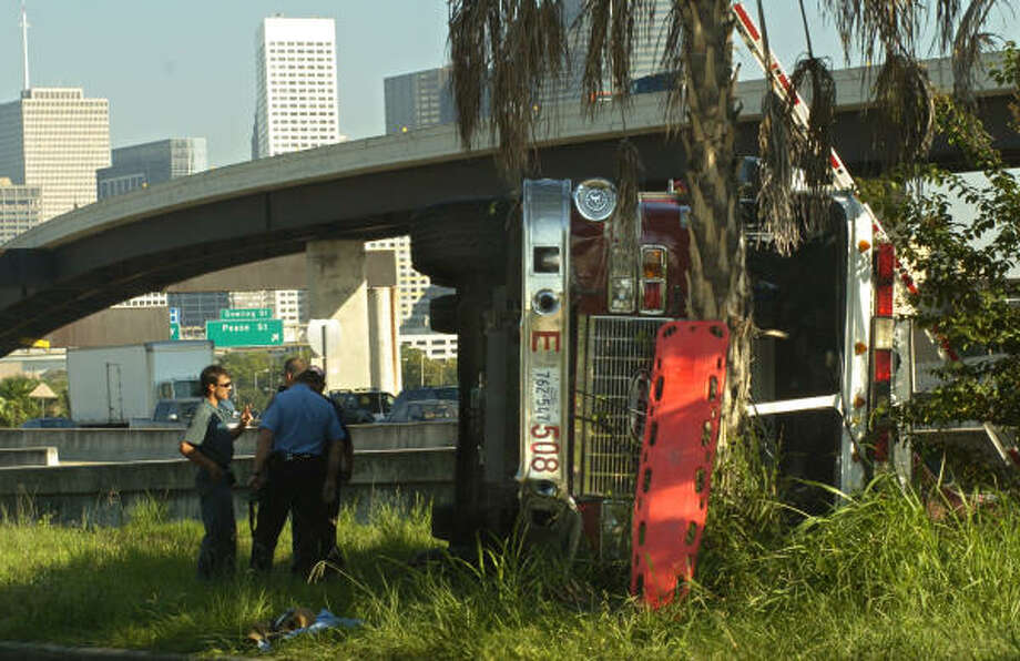A Houston Police officer and tow-truck crew get a closer look at an overturned fire truck on the Gulf Freeway feeder road near Sampson today. Photo: Johnny Hanson, For The Chronicle