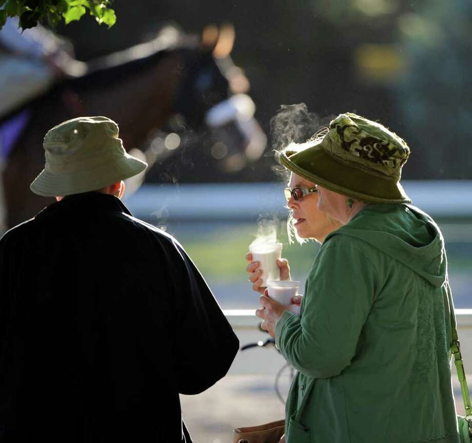 Racing fans hold hot coffee as they watch the morning workouts at the main track at the Saratoga Race Course in Saratoga Springs, New York Aug 11, 2011.    (Skip Dickstein / Times Union) Photo: SKIP DICKSTEIN