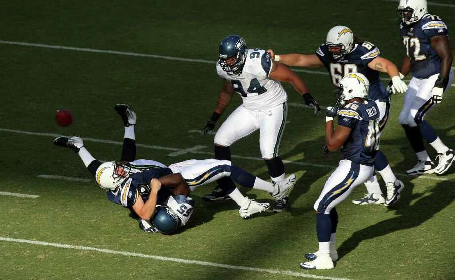 Quarterback Billy Volek #7 of the San Diego Chargers gets sacked by Jimmy Wilkerson #65 of the Seattle Seahawks. Photo: Donald Miralle, Getty Images / 2011 Getty Images