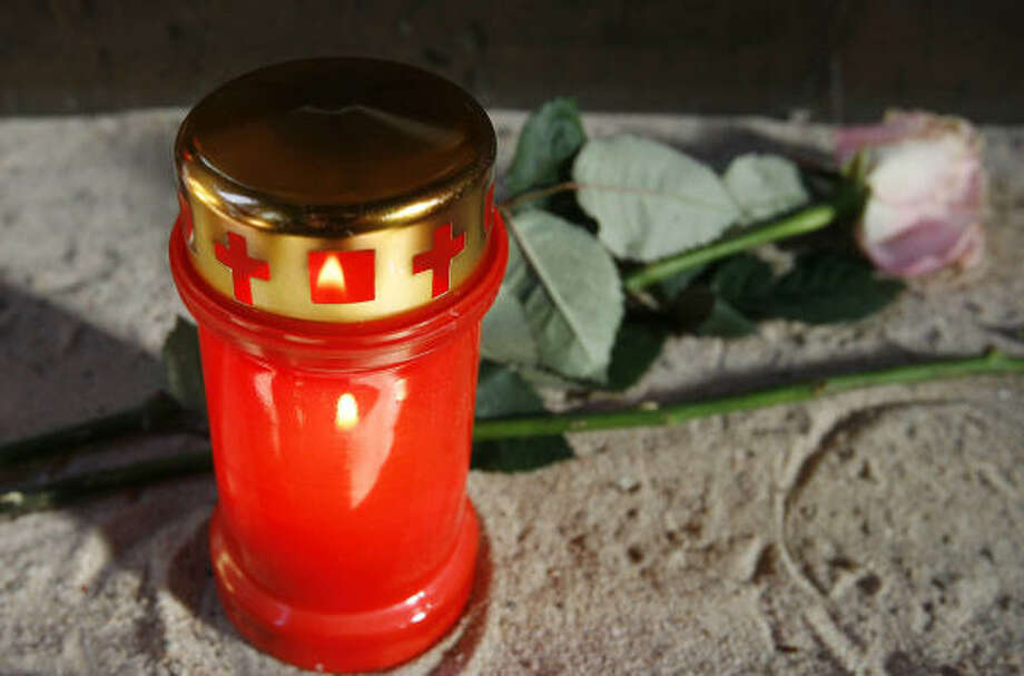 A candle stands at St. Augustine Monastery in memory of the Rev. Roland Weisselberg, 73, who set himself ablaze outside the church. Photo: JENS MEYER, AP