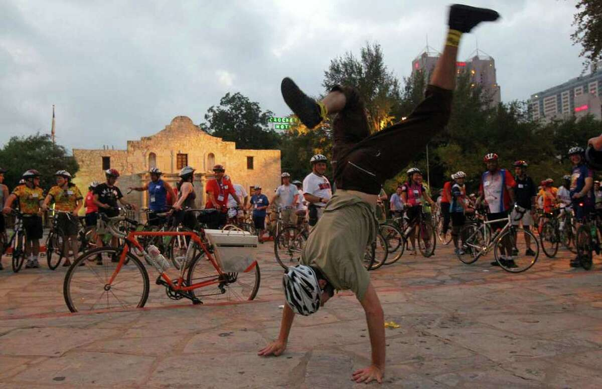 Jack Sanford, the BikeTexas art director, does a handstand in front of the Alamo before heading out on his bike with other cyclists who are attending the National Conference of State Legislatures.