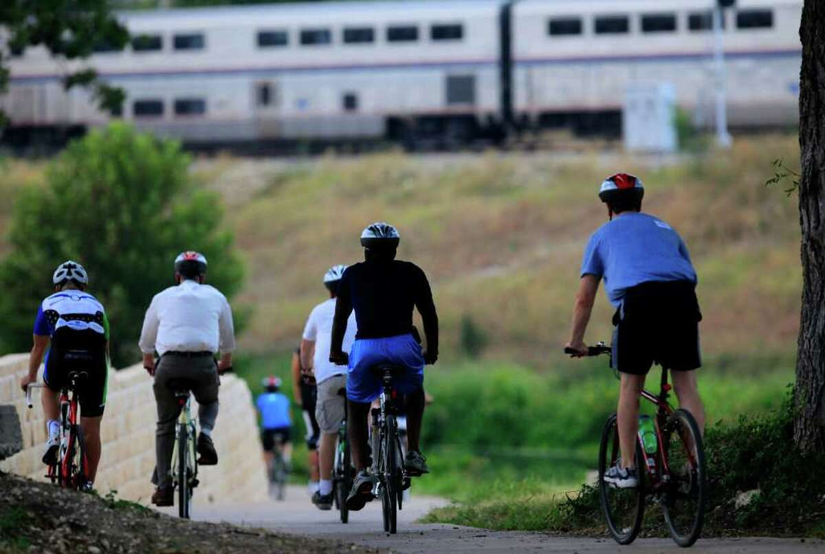 Cyclists attending a ride with the National Conference of State Legislatures head down the Mission Reach of the San Antonio River on Thursday, August 11, 2011. The group started at the Alamo and headed south towards Espada Dam. An Amtrak train (background) is sidetracked waiting for a freight train to pass.