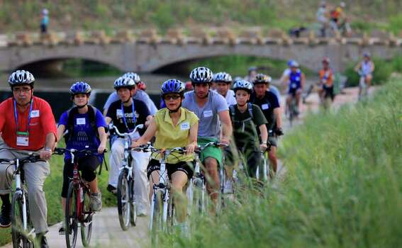 Cyclists with a group of people from the National Conference of State Legislatures pass tall grass on the Mission Reach of the San Antonio River on Thursday, Aug. 11, 2011. The group is in San Antonio for a convention. Photo: John Davenport/jdavenport@express-news.net